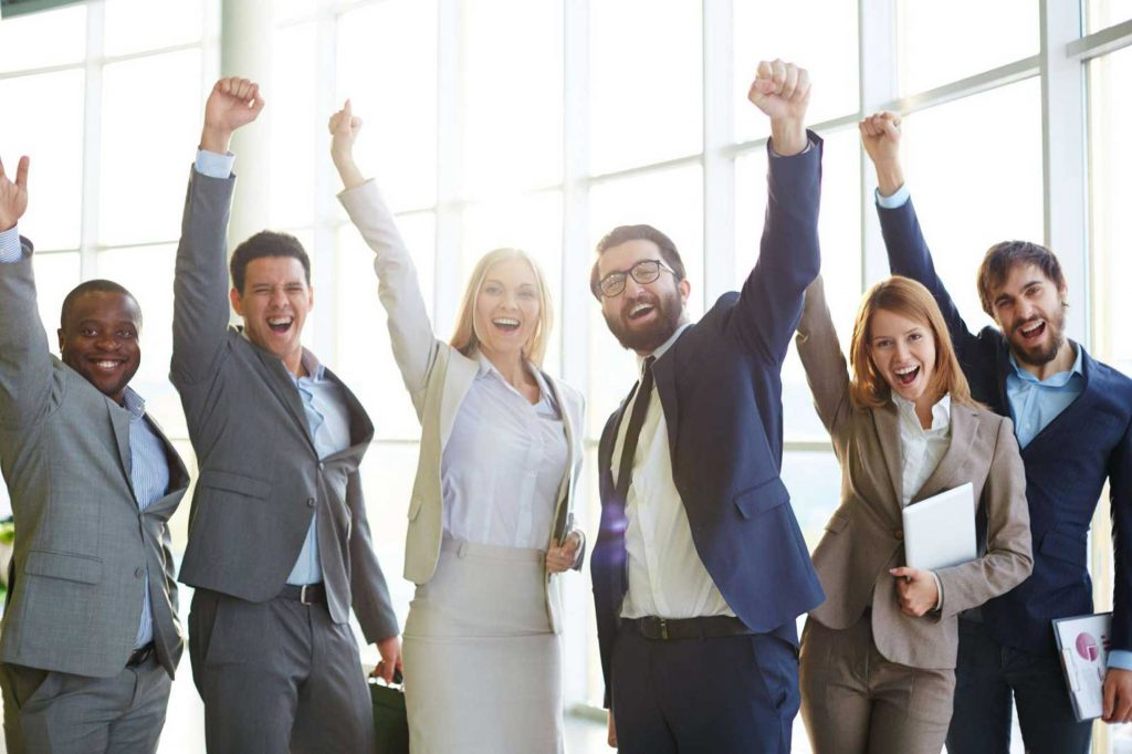 6 people dressed in business attire each with one arm up and excited faces.