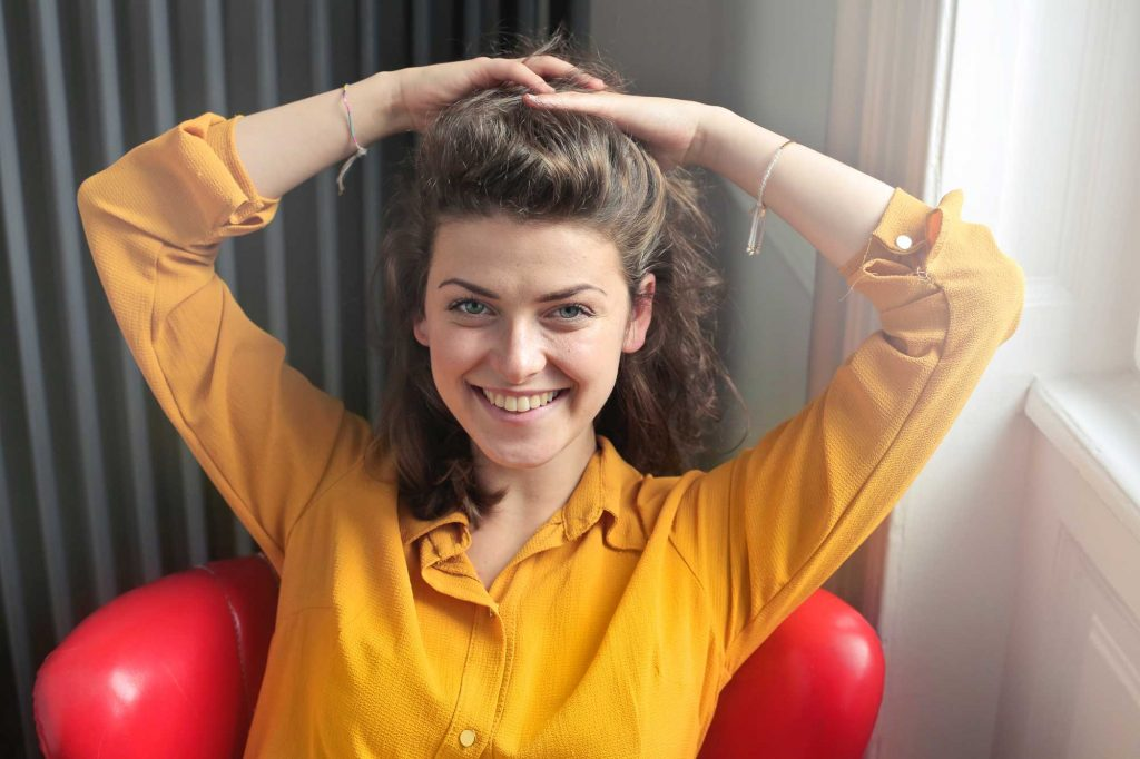 A woman smiles as she sits in a bright red chair and has both hands in her hair.