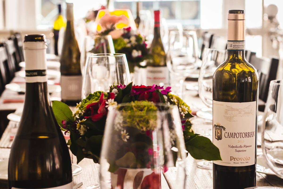 A large dinner table with wine bottles, glasses, plates, and colorful flower bouquets.