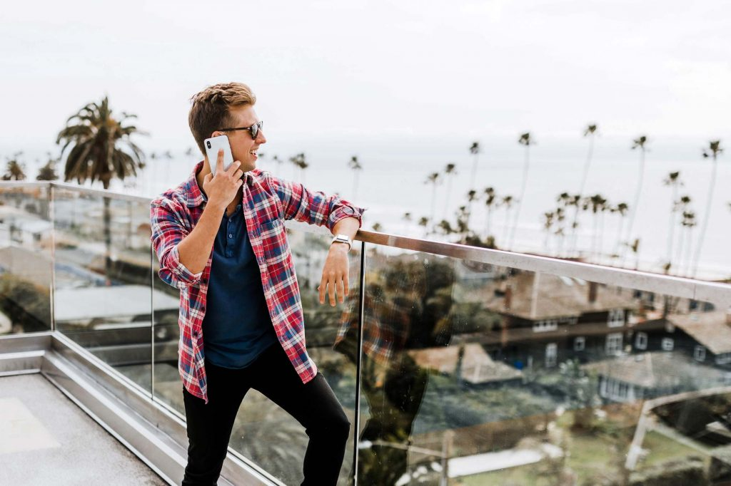 A man leaning against a railing as he takes a phone call and looks to the ocean view.
