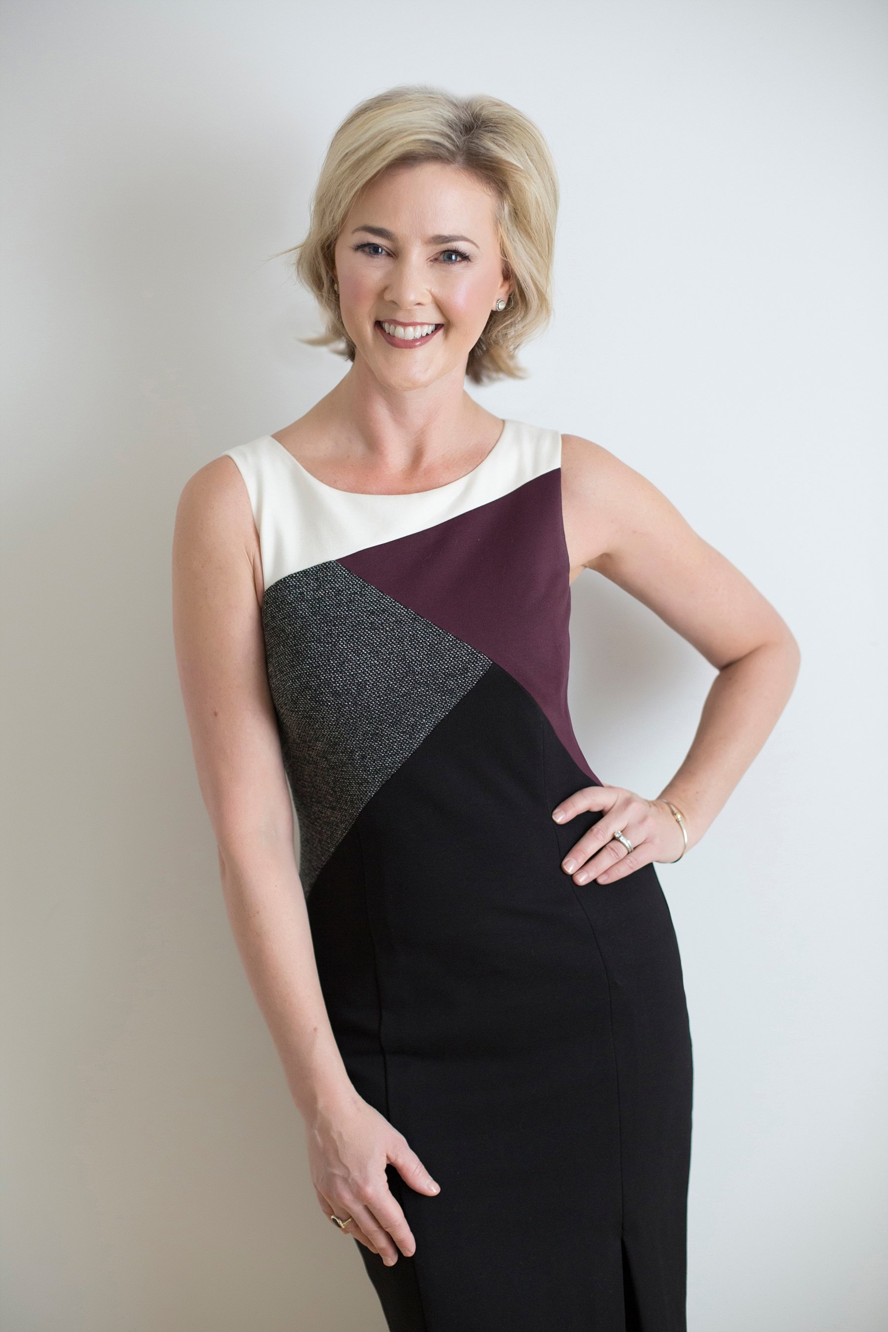 Allison Dunn in a dress as she smiles and poses with one hand on her hip.