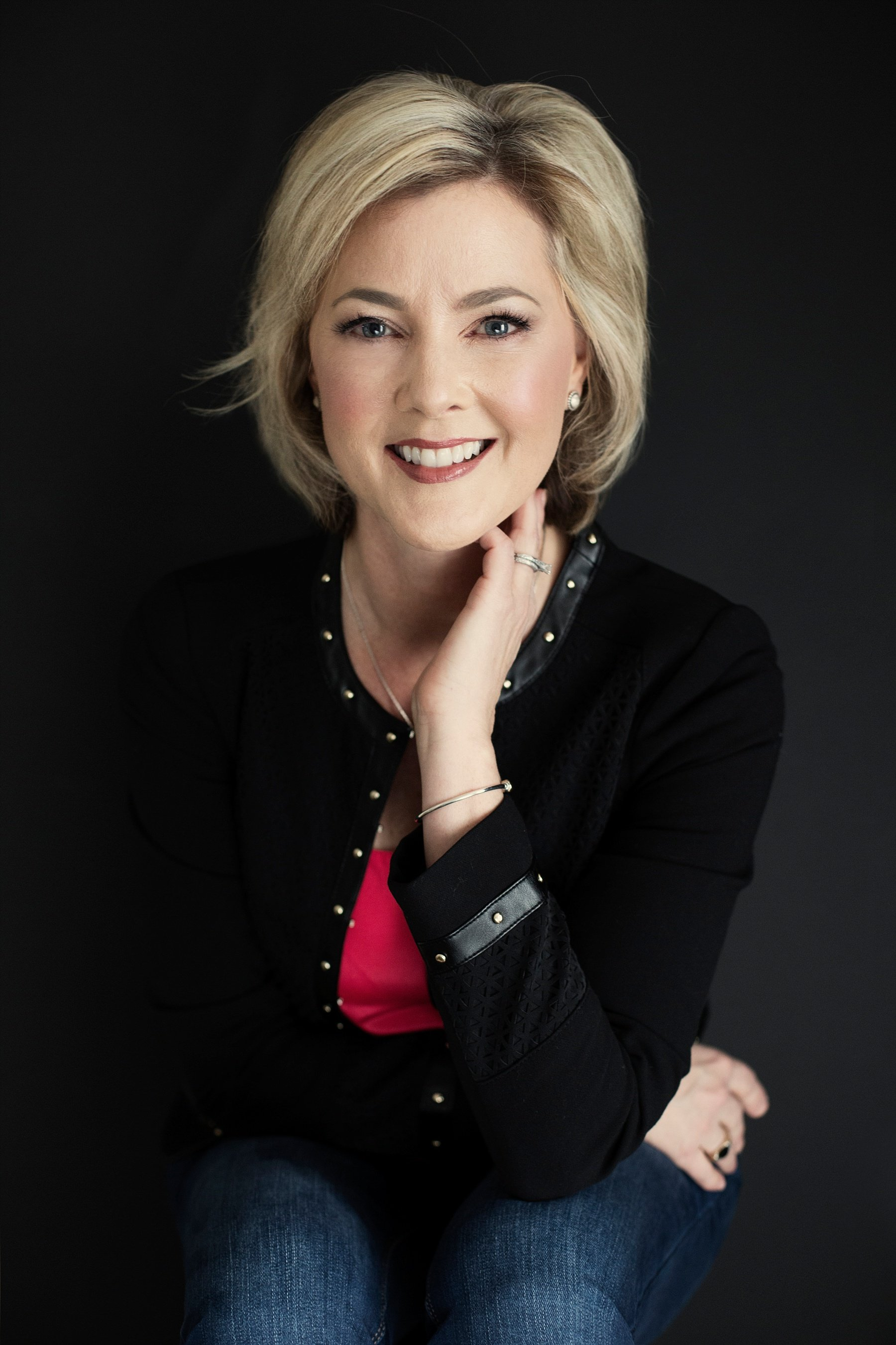 Allison Dunn in a black cardigan smiling as she sits and poses against a black background with one hand rested against her face..