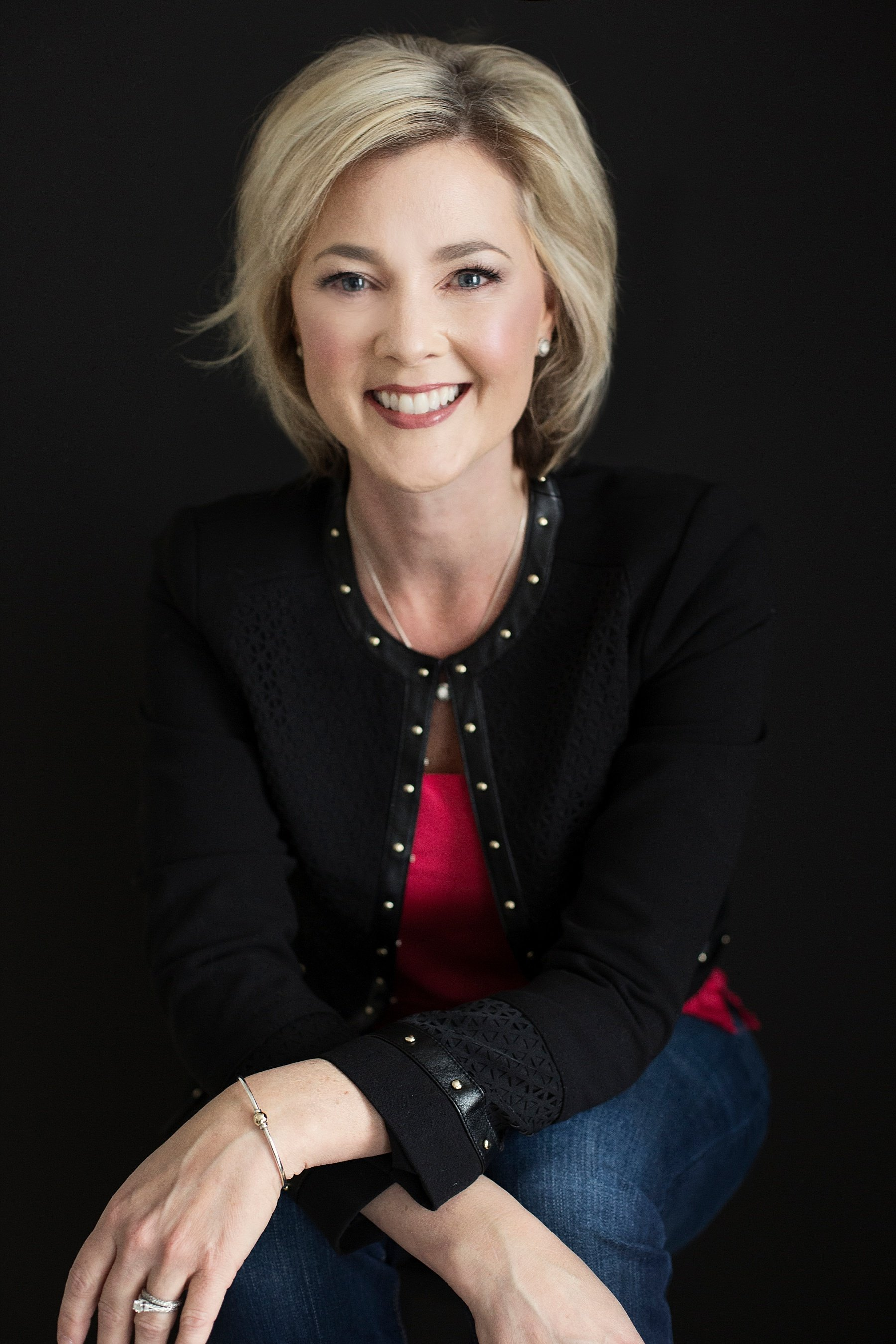 Allison Dunn in a black cardigan smiling as she sits and poses against a black background.