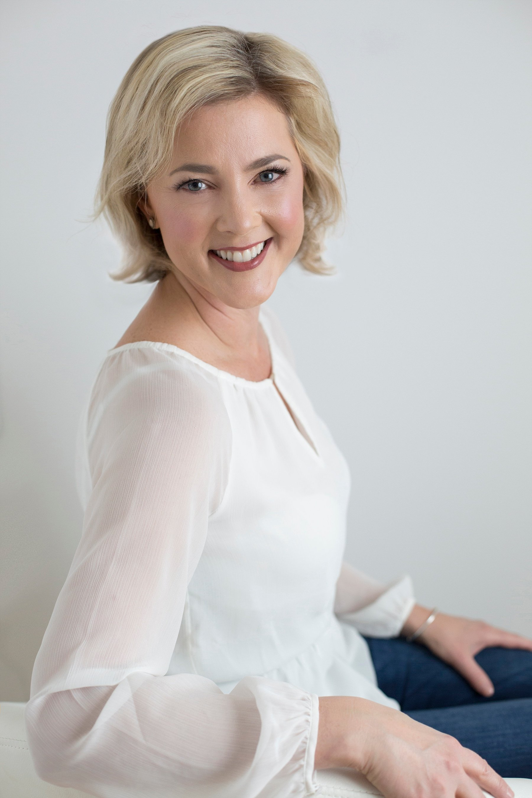 Allison Dunn in a white blouse smiling as she sits on a white leather couch.