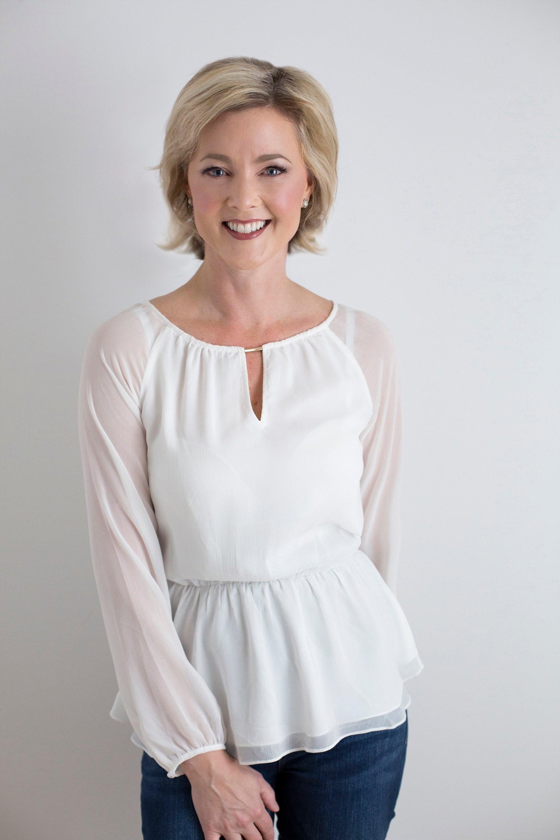 Allison Dunn in a white blouse smiling as she poses against a white background.
