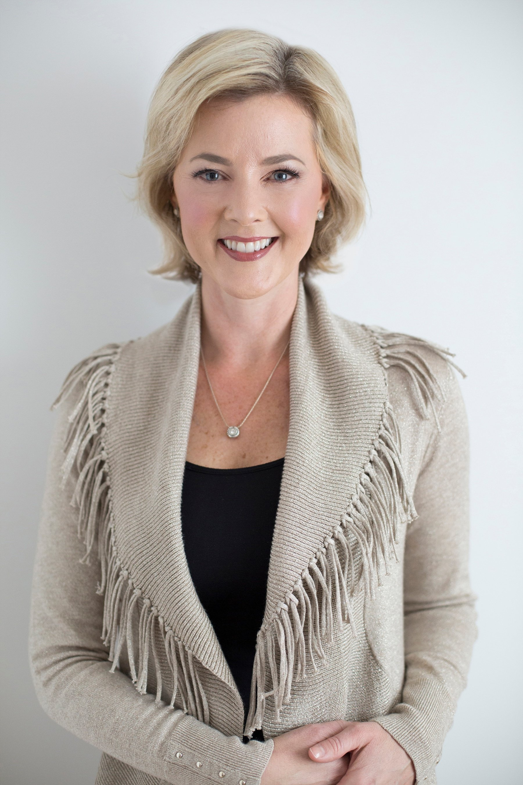 Allison Dunn in a tan sweater smiling as she poses with both hands placed on her left hip.