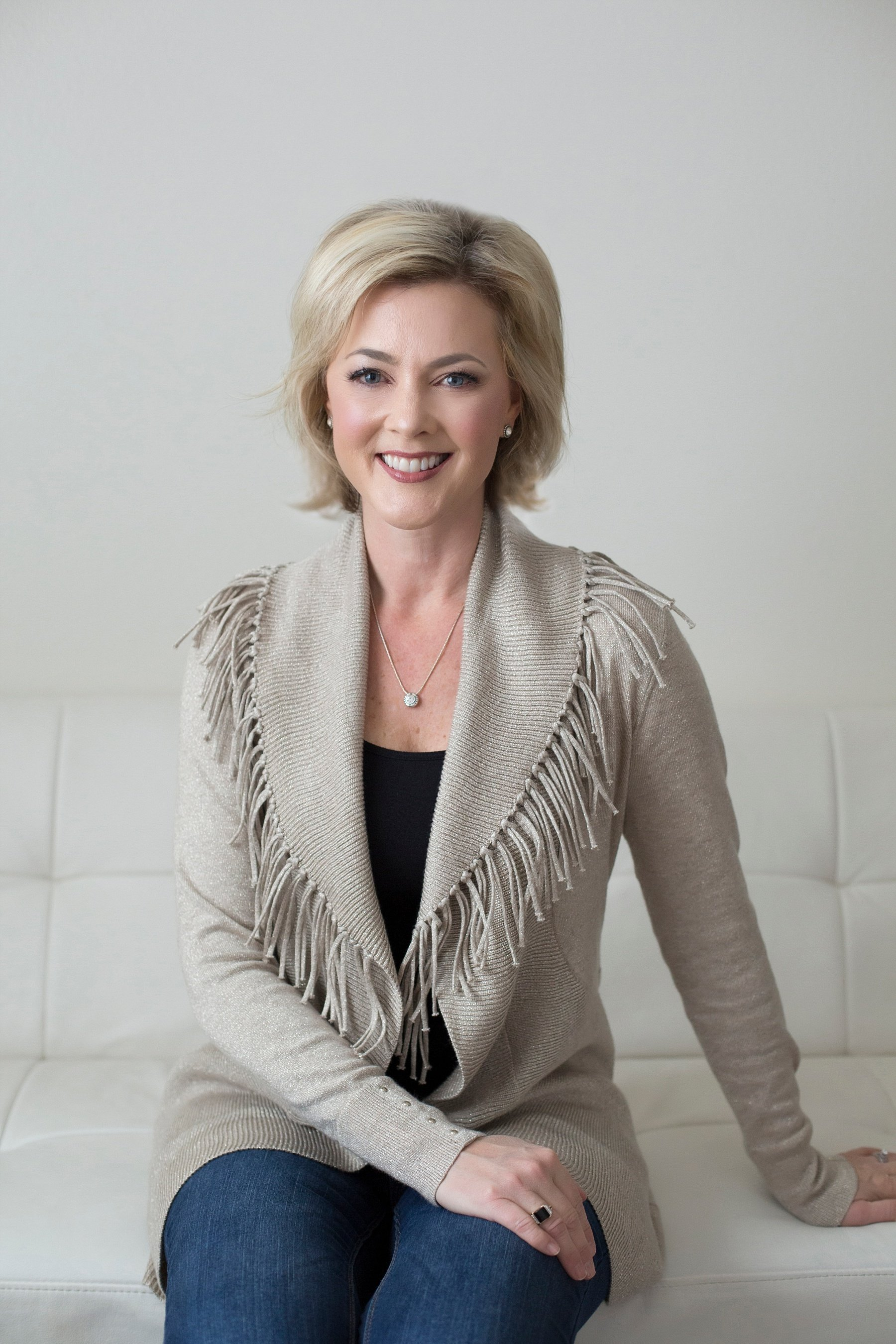 Allison Dunn in a tan sweater smiling as she sits on a white leather couch.