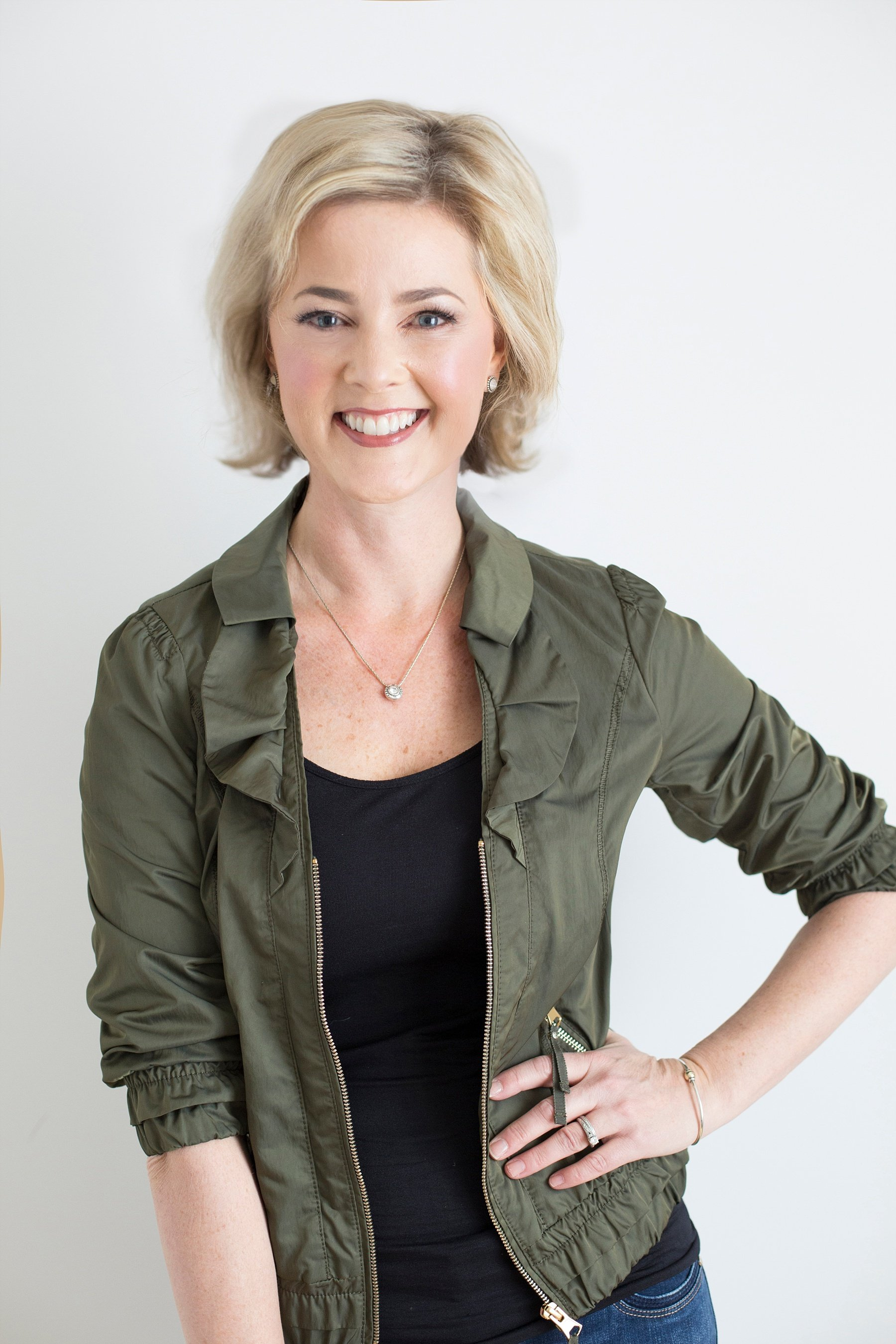 Allison Dunn in an army green jacket posing with her arm on her hip.