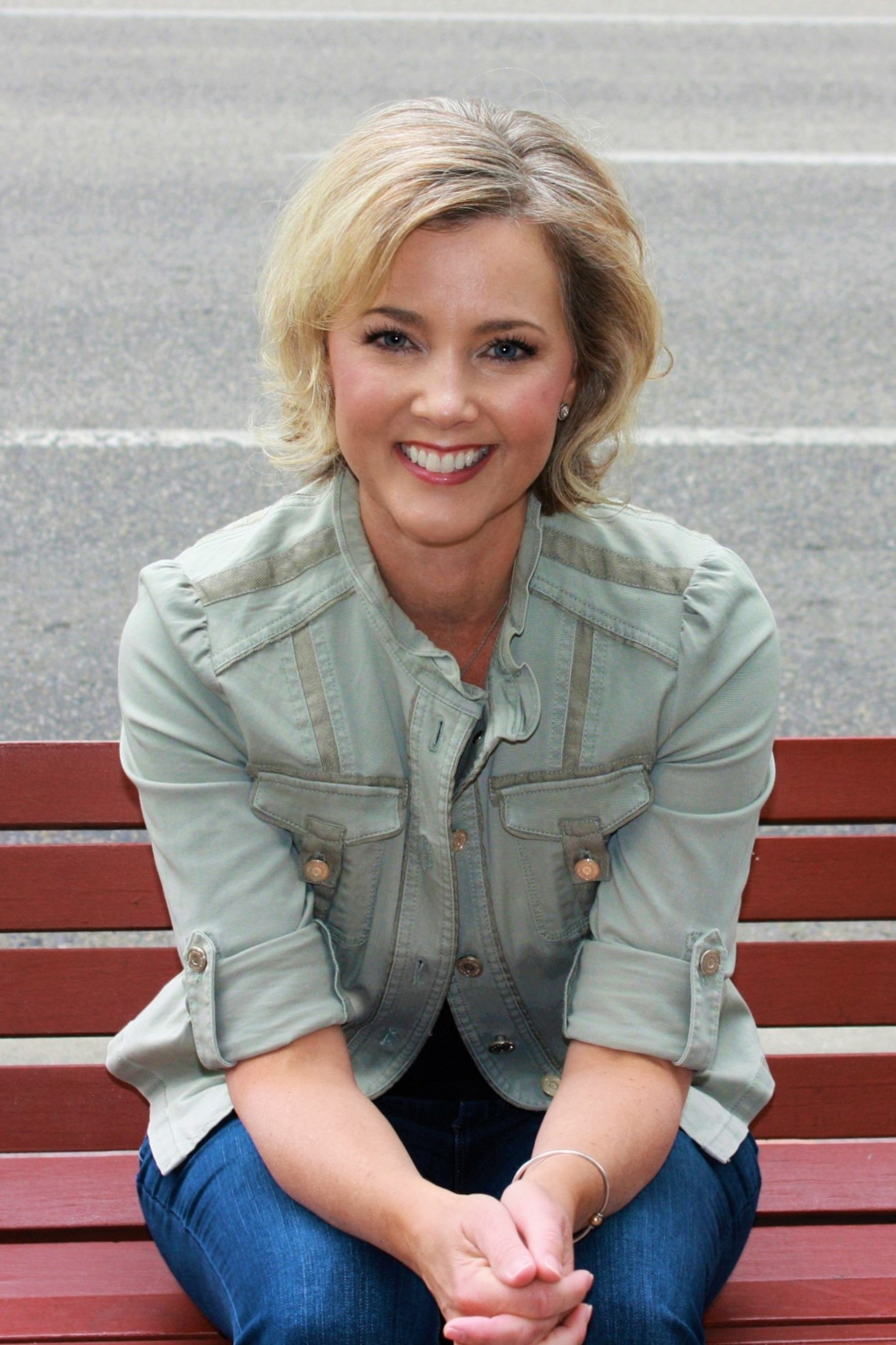 Allison Dunn in a green button up on a red bench.