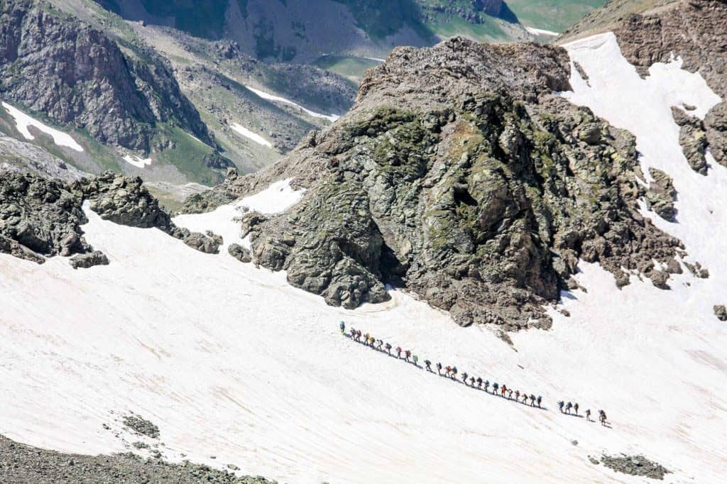 A trail of hikers as the walk up a snowy mountain