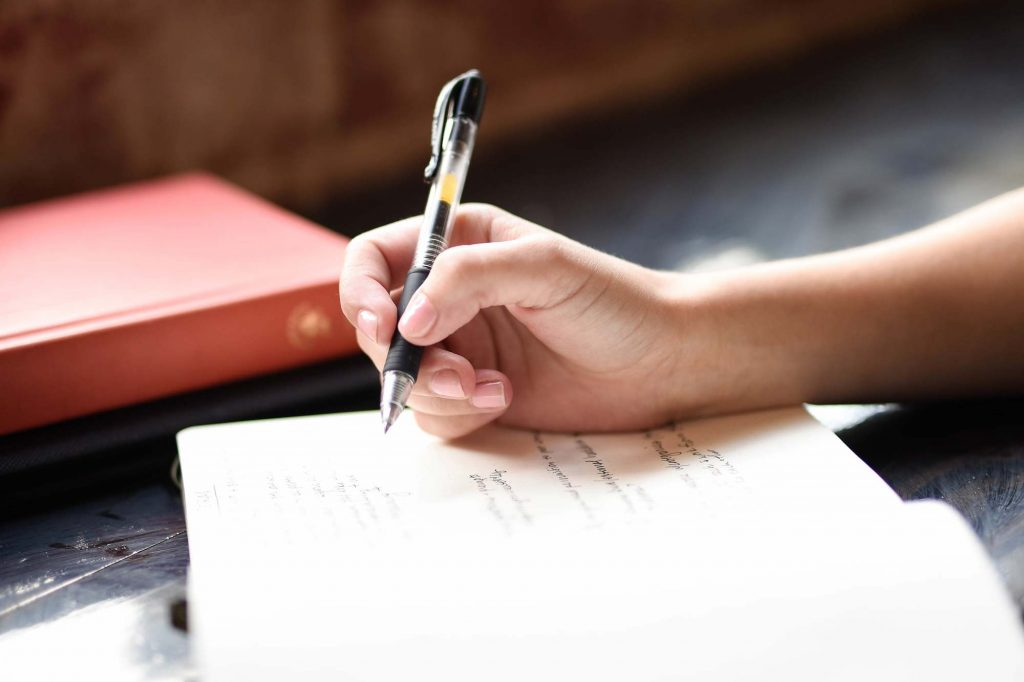 A pen lifted to reveal writing in a notebook