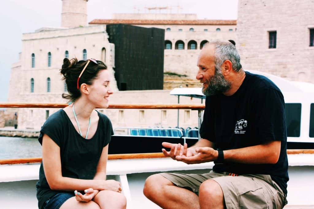 Two people smiling as they converse on a boat in the water