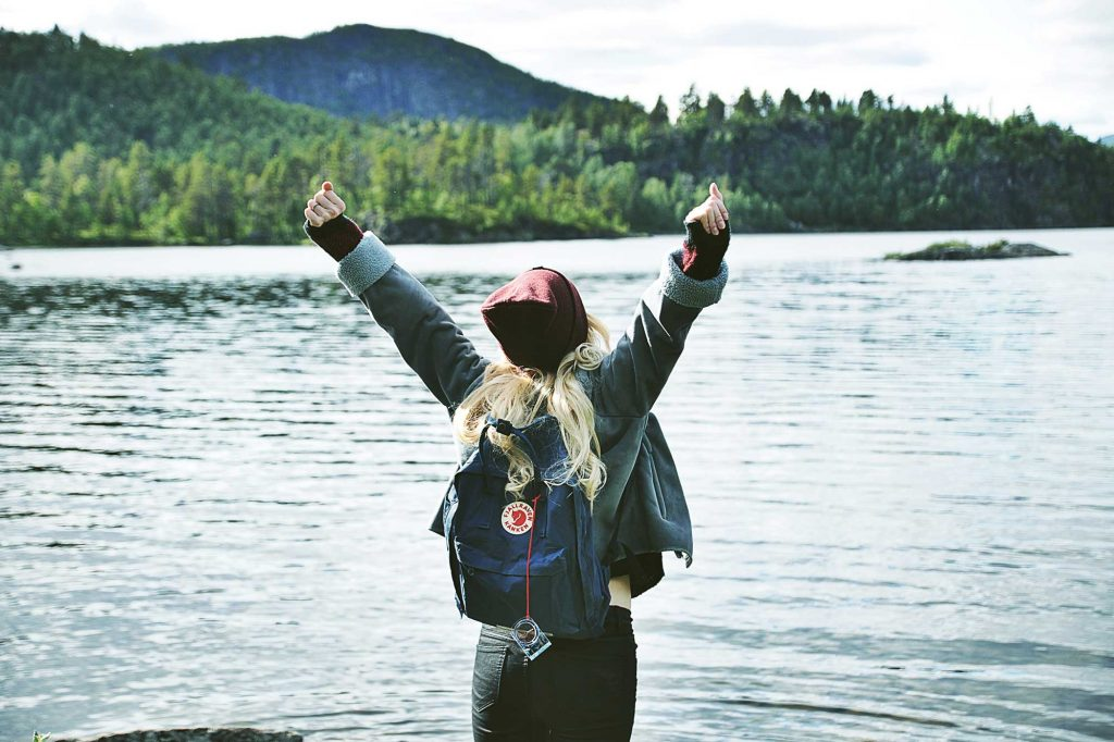 An outdoor person with their arms stretched out as they're surrounded by water and forestry.