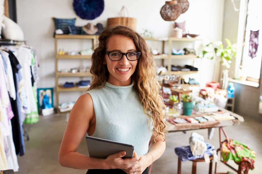 A woman in a small store smiling as she holds a closed laptop