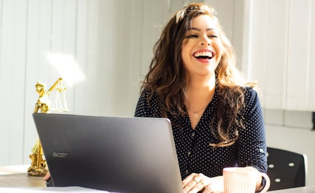 Picture of a woman smiling and working on her computer.