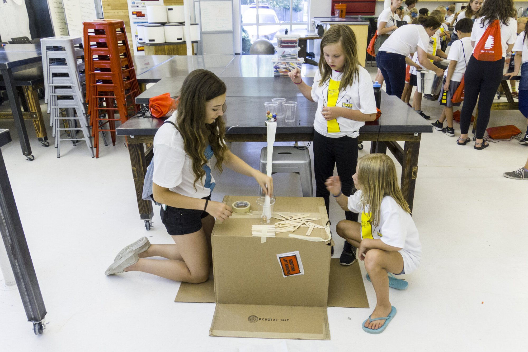 Three girls working on a project during a Youth Group Charity Event.