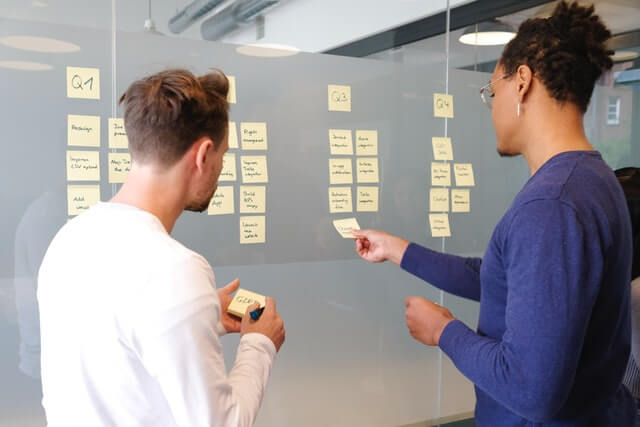 Two people organizing sticky notes on an office wall.